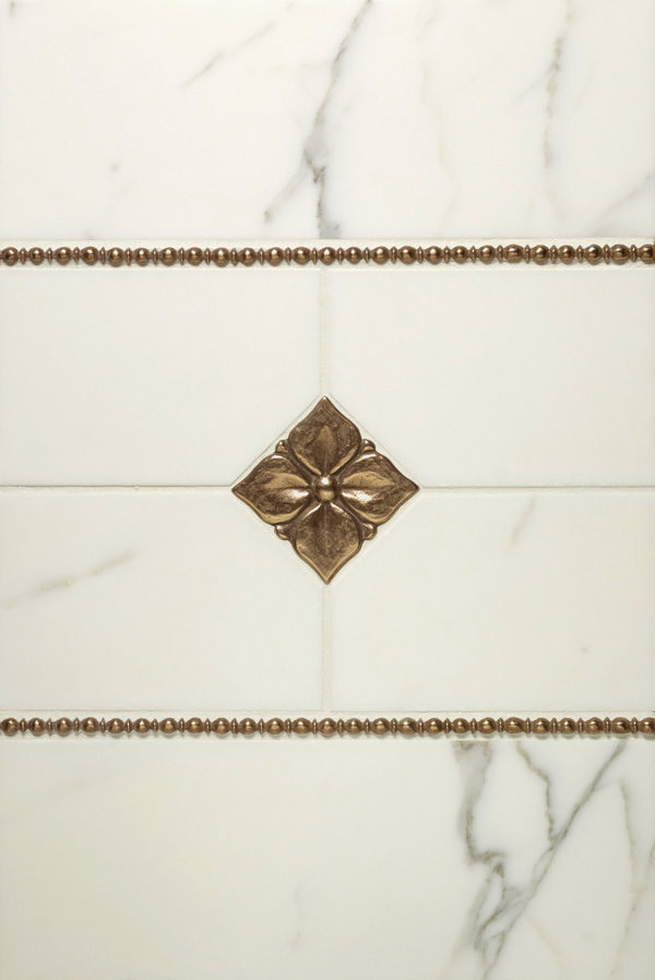 Hand-carved metal accent tiles in solid bronze and zinc