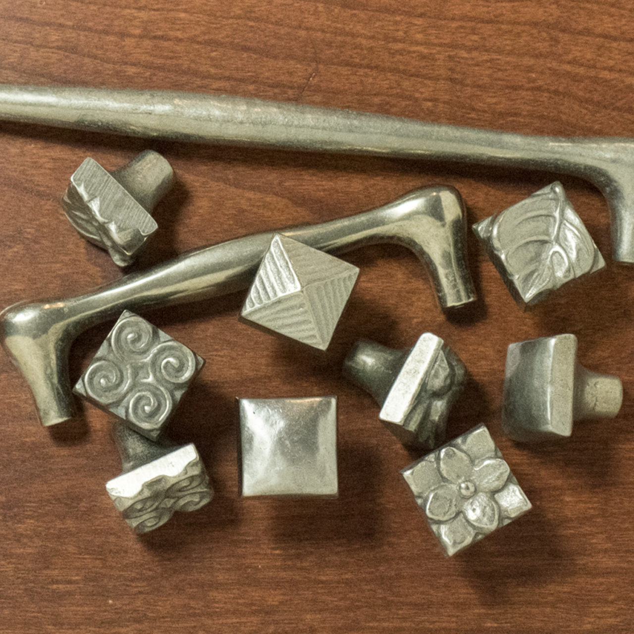 Foundry Art bronze accent knobs and pulls on wood