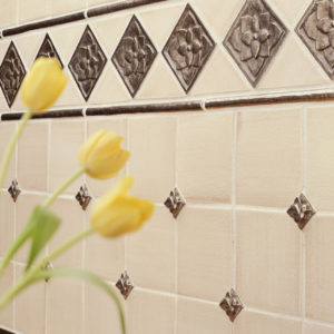 Foundry Art Carved Half-Round liner, Lotus 3-inch, and Dove metal accent inset tile off-white ceramic tile backsplash