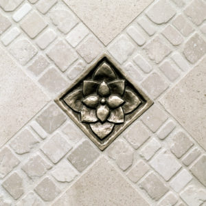 traditional bronze tile accent inset white stone floor Lotus