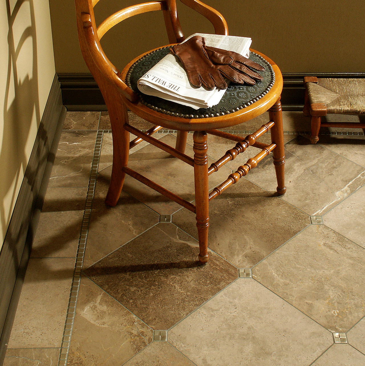 Metal accent tiles and liners: Mosaic Liner and Terrace in Traditional Bronze set in a limestone floor