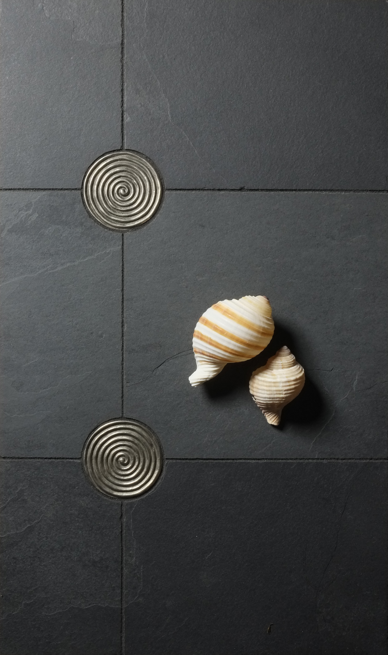 Metal accent tiles: Petroglyph in White Bronze with black stone