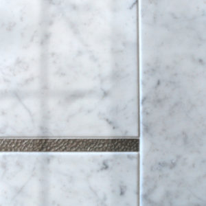 Bronzework Studio Classic Water Song metal accent liner tiles with white marble