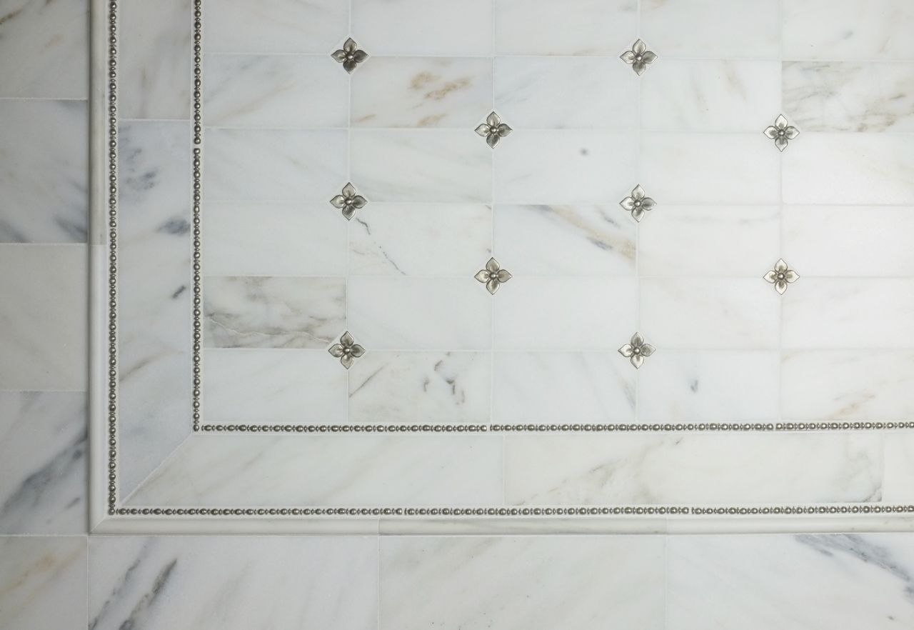 Metal accent tiles and liners: Roman Liner and two sizes of Blooming Leaf in White Bronze with white marble
